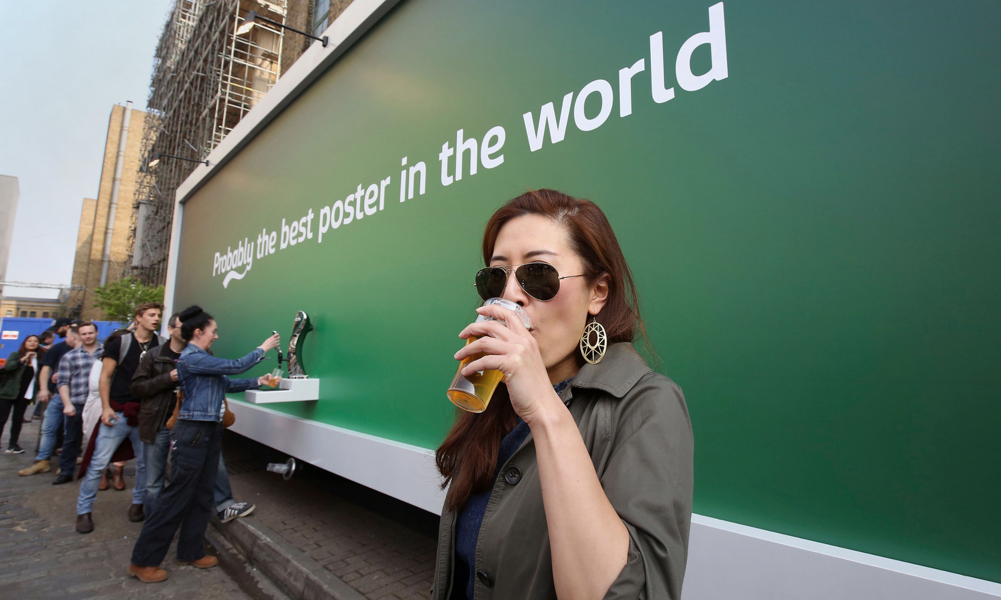 Sylvia Wong with her free Carlsberg beer at the Truman Brewery in London after the brewing company created the world's first beer dispensing billboard. PRESS ASSOCIATION Photo. Picture date: Wednesday April 8, 2015. Photo credit should read: Philip Toscano/PA Wire